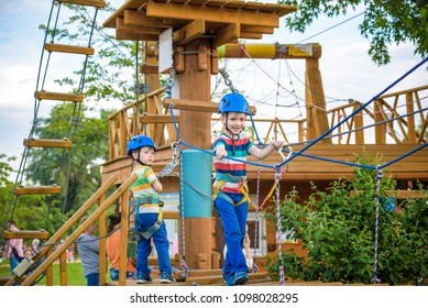 Twin brothers in helmet walks by rope at park sunny summer day in adventure playground. Active healthy leisure time spending concept with children.