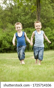 Twin brothers holding hands in park, smiling