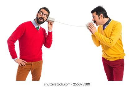 Twin brothers talking through a tin phone