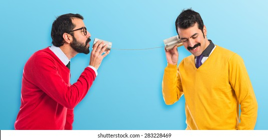 458ac32b16 Twin brothers talking through a tin phone over colorful background