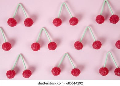 lot of Twin Cherry Lollipops like an old time ago on a pink background with blur effect.