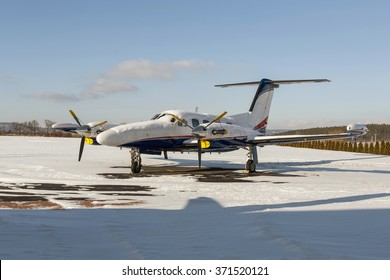 Twin engine aircraft with turboprop power plant on runway under snow in sunny winter day.