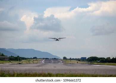 twin engines propeller aircraft take off from runway and climb with cloud and sky background and copy space