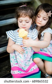 Twin girl tries stealing ice cream from the other child