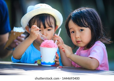 Twin girls eating shaved ice
