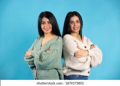 Twin girls in identical clothes on a blue background, braided their hands and look at the camera. Side space.