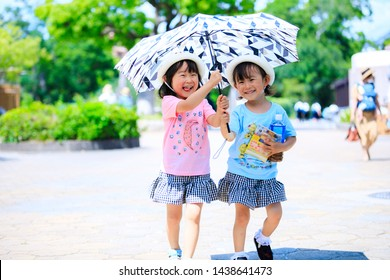 Twin girls playing with parasol