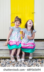 Twin girls sisters share a joke laughing together on a summer beach