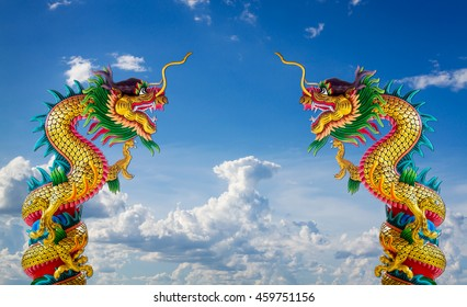 Twin Golden Chinese dragon statue in blue sky background