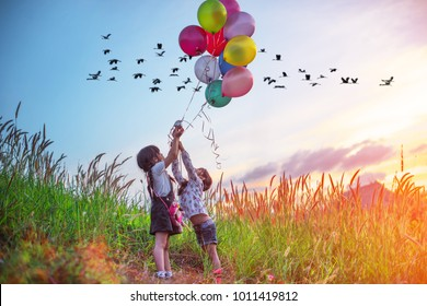 twin kids running on the meadow on the hills with holding in hand multicolor ballons and flock of birds in background