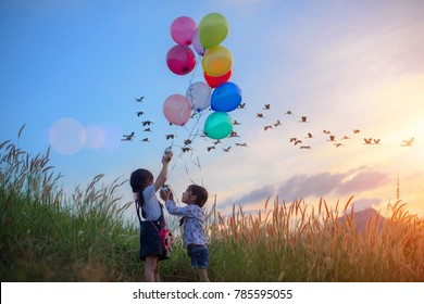 twin kids running on the meadow on the hills with holding in hand multicolor ballons, flock of bird flying over medow in background