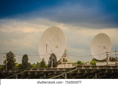 Twin large scale white satellite dish in solar farm under dramatic blue and cloudy sky background.
