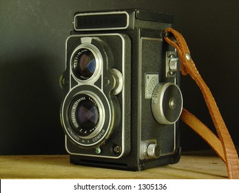 Twin lens reflex camera on wood shelf with leather strap