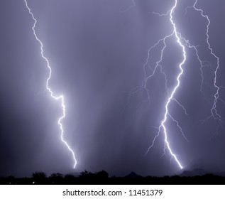 Twin lightning bolts strike a mountain foothill and a stand of saguaro cacti