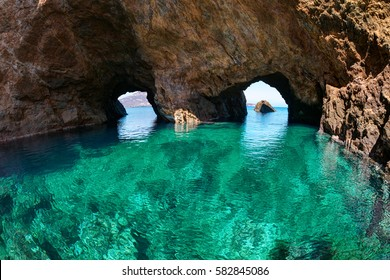 Twin natural rocky arches with clear transparent waters, in Tragonissi islet, Myconos, Greece