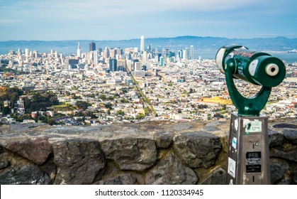Twin peaks view of amazing Bay Area San Francisco California cityscape skyline vast rooftops and buildings in big city on a slope with pedestrian viewing area binoculars