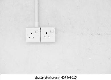 Twin power socket on a blank concrete wall. Processed in monochrome.