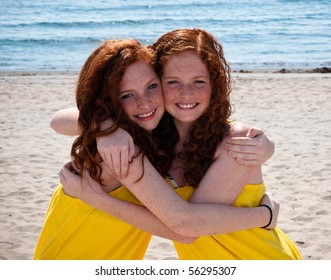 Twin Red-Headed teenage girls playing at the beach