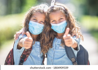 Twin sisters with face masks go back to school during the Covid-19 quarantine and showing thumbs up.