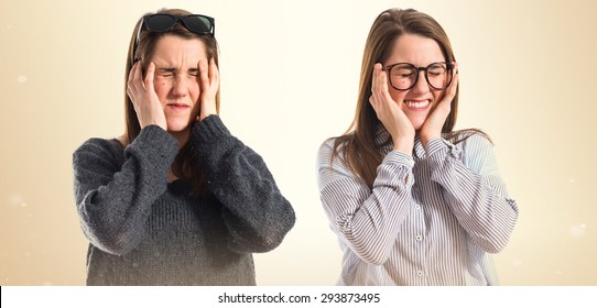 Twin sisters with headache over ocher background