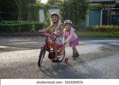 twin sisters helping each other while learning how to ride a bicycle