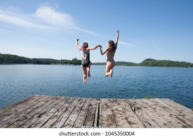 Twin sisters jump off a dock into a lake.