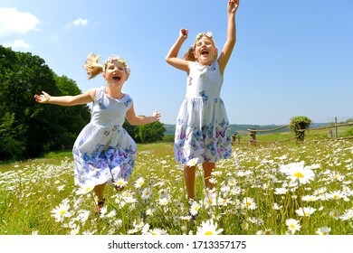 Twin sisters play together in a daisy field  and smile cheerfully at the camera. They both jump up and down while laughing.