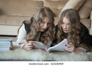 twin sisters read the book lying on the floor