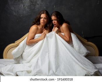 Twin sisters sitting on the bed and screaming in terror on a dark background.
