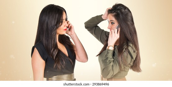 Twin sisters talking to mobile over ocher background
