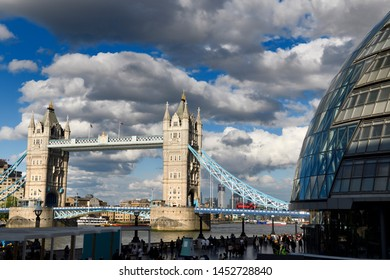 Twin stone towers and suspension bridge of Tower Bridge over the Thames River in London with modern curved City Hall building London, England - June 8, 2019
