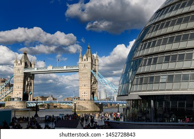 Twin stone towers of Tower Bridge over the Thames River in London with modern curved City Hall building London, England - June 8, 2019