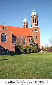 The twin towers of Saint Joseph's Chapel on the campus of Saint Joseph's College in Rensselaer, Indiana with green grass and a bright blue sky vertical