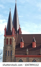 twin towers and steeples of romanesque revival style church exterior and roof above nave in minneapolis minnesota