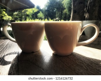 Twin white cup soft focus on wooden table with sunshine reflection. Left cup have  Red lipstick color as lips dirty on edge after woman sip the tea opposite with right cup that sip by man.