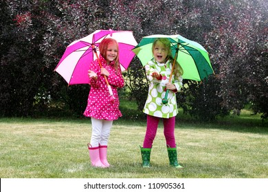 twin young girls playing in rain with coats, umbrellas and boots