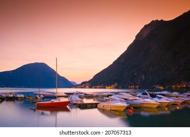 Twinkling village lights, sunset mountain backdrop and glassy waters on the beautiful Lake Lugano Italy.