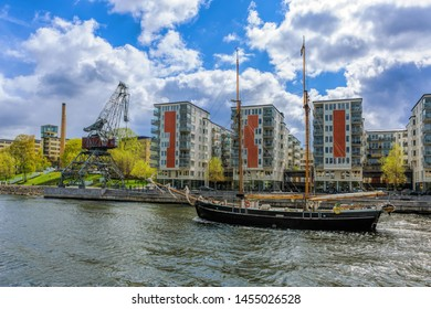 Twin-masted sailing ship passes underway of the canal Hammarby in Stockholm at sunny spring day.