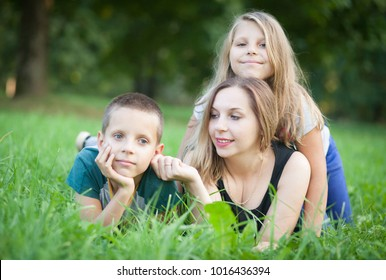 twins boy and girl 9 years old and mom  on the grass in the park
