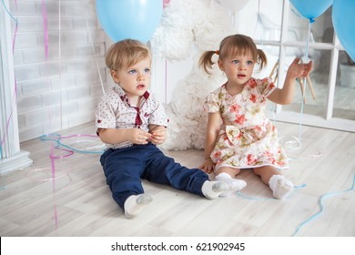 Twins boy and girl birthday with balloons