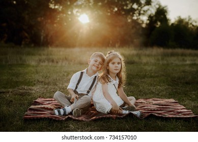Twins brother and sister sitting in a meadow against the sunset background