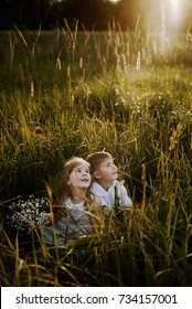 Twins brother and sister are sitting on the meadow and watching the sunset