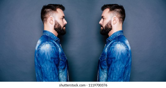 Twins concept photo. Young handsome bearded twins brothers in denim wear looking on each other isolated on gray