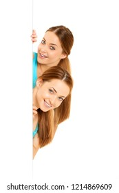 Twins, girls models. Two smiling women holding a banner, poster with place for your text, isolated over a white background.