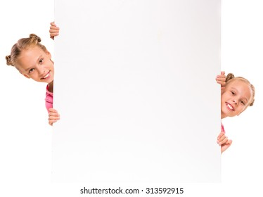 Twins girls are showing blank signboard or copyspace for slogan or text, isolated over white background.
