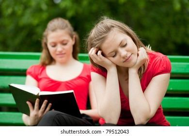 twins girls sitting on a bench reading a book