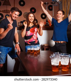Twins playing beerpong with beautiful brunette in bar. square photo