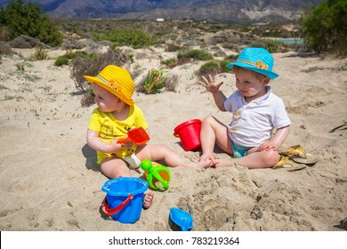 Twins playing in the sand on holidays in Greece