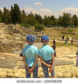 Twins standing & watching a performance on the arena of a ruined amphitheater. Twin boys dressed the same. Chersonesus amphitheater ruins in Sevastopol. Khersones ancient ruins of the amphitheater.