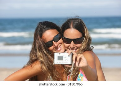 twins taking a photo of themselves on the beach